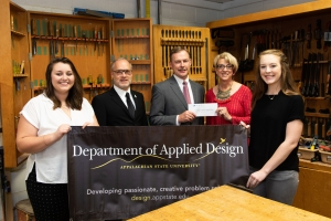 From left to right, interior design senior Hannah Downs, Department of Applied Design Chair Brian Davies, La-Z-Boy's vice president of human resources, Tim Solesbee, College of Fine and Applied Arts Dean Phyllis Kloda and interior design senior Hailey Estes pose in the department's wood shop. Kloda and Solesbee are holding the $75,000 check made to the department by the La-Z-Boy Foundation, which will fund L.I.D.A. — the student-designed Lab for Innovating in Design at Appalachian. Photo by Chase Reynolds